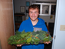 Liam with fresh veggies from the greenhouse